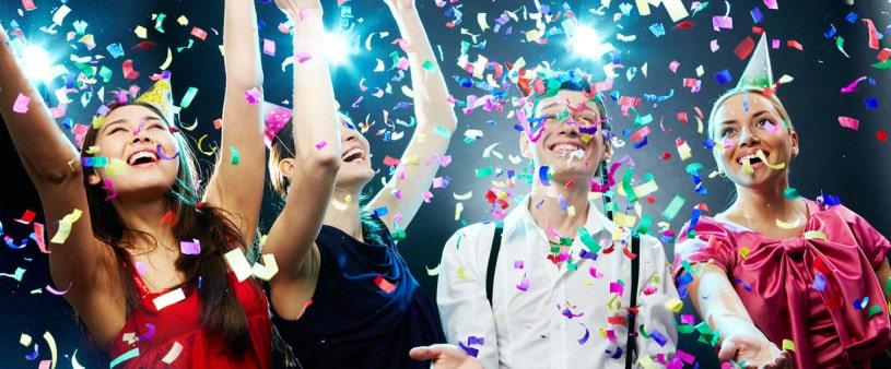 festive Four friends making having fun among confetti